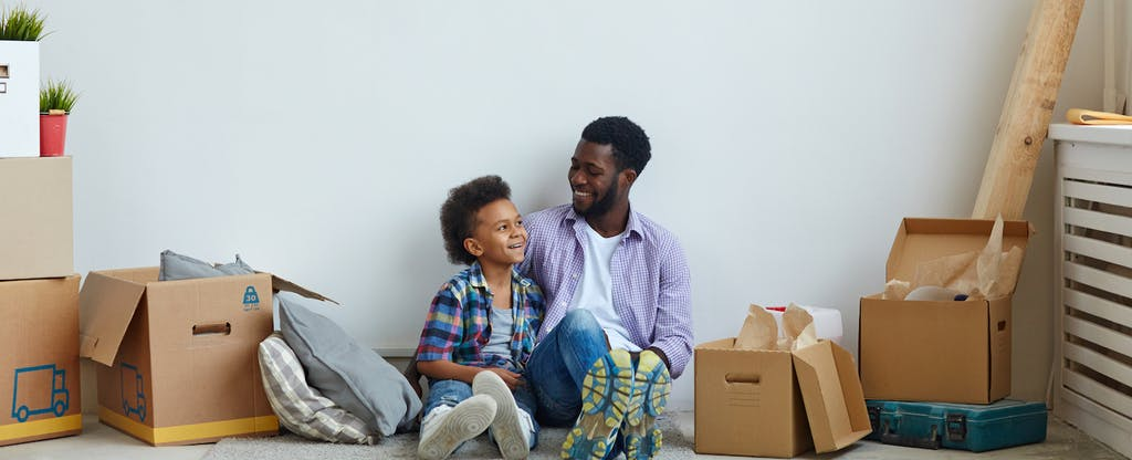 Father sitting with his child surrounded by moving boxes and contemplating a personal loan.