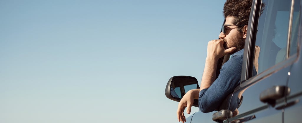 A man wearing sunglasses leans out of his car window, staring pensively into the distance.