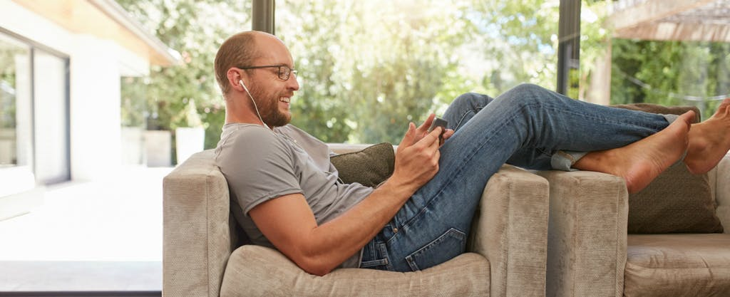 Man with earbuds in his ears sitting across an armchair smiles while he looks at a tablet screen.