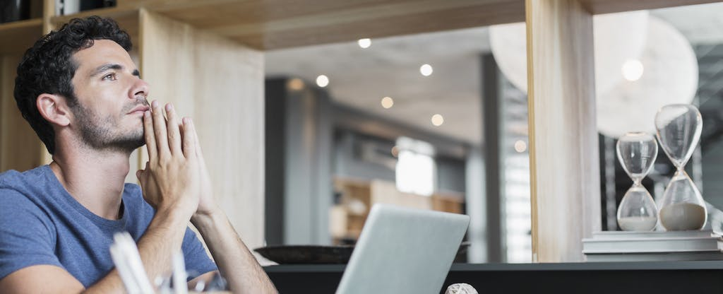 Pensive man at laptop thinking about aggressively paying down his debt and wondering whether it was worth it