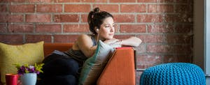 Woman sitting on a couch thinking about whether she should get a personal loan or do a balance transfer.