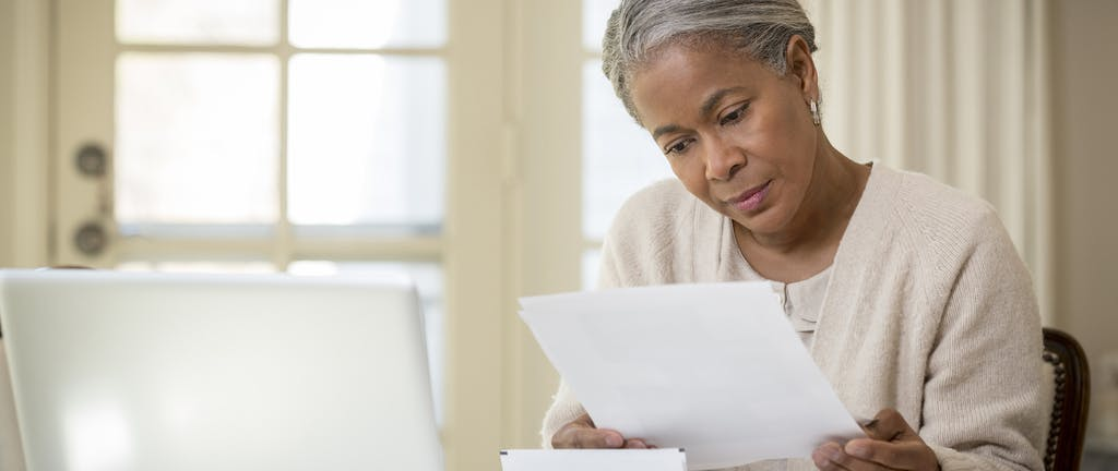 Older woman considers papers at her table with her laptop in front of her