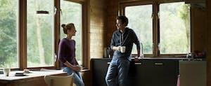 Couple having coffee in a cottage and chatting about their personal finances.
