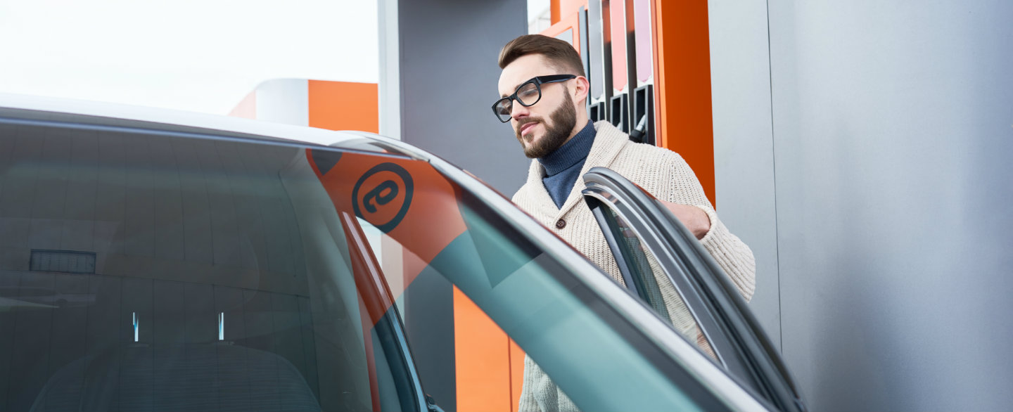 Man with glasses and a beard opening his car door at a gas station and contemplating the costs of becoming a Lyft or Uber driver.