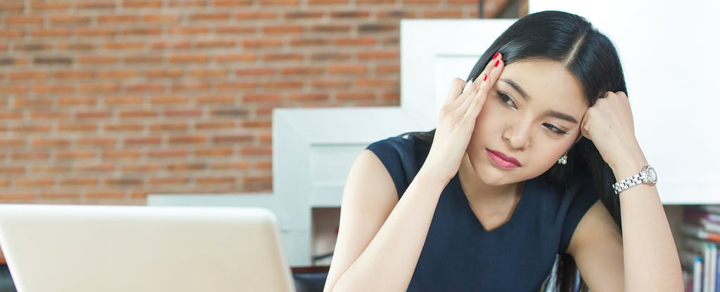 """Frustrated young woman staring at a computer and wondering, """"Why is my account reported as closed?"""""""