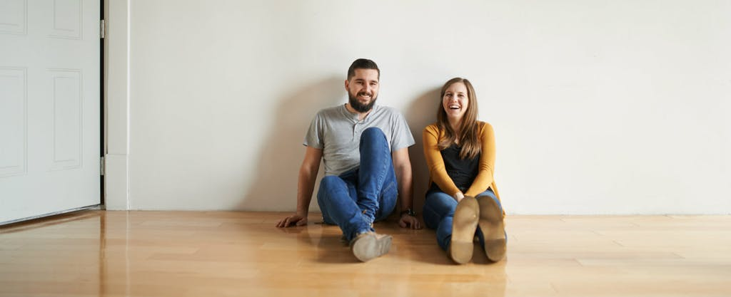 A smiling man and woman sit on the floor of their new home.