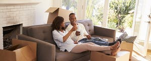 Couple On Sofa Taking A Break From Unpacking On Moving Day. They already figured out how big their down payment had to be.