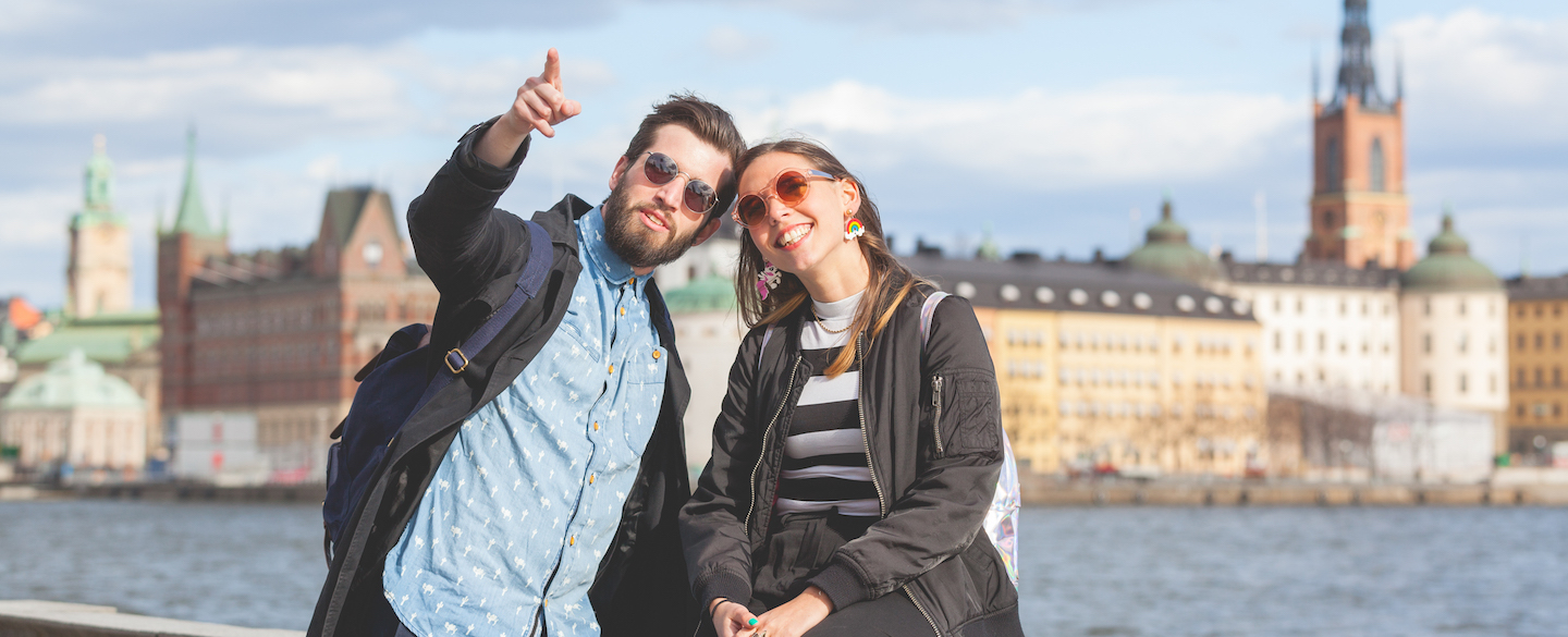 Happy young tourists in Sweden discussing how the country is almost cashless and how other countries could learn from Sweden.