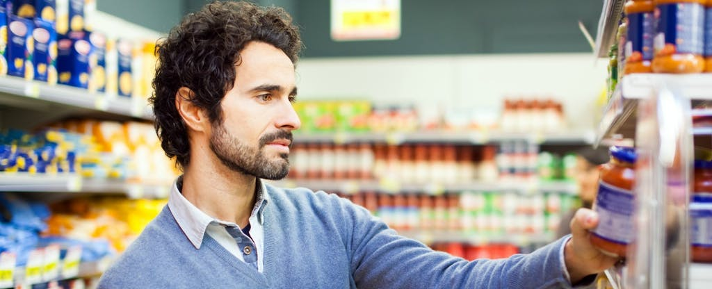 Man in a grocery store holding a jar and mentally comparing the 7 best credit cards for groceries