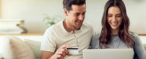 Couple looking at a laptop to find out what the best credit card offers are for new credit cards in 2017