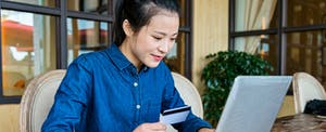 Young woman holding a credit card and using a laptop to find the 5 best Visa credit cards