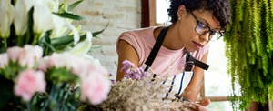 Flower shop owner leaning on her counter and wondering how to build business credit even with poor personal credit