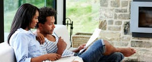 Young couple sitting in their living room and reading about the steps to build a solid financial foundation