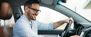 Smiling man in a rental car, happy because he learned how to get car rental insurance from your credit card