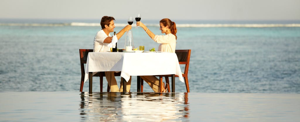 Couple sitting at a table in the surf at a beach, toasting because they have the Centurion® Card from American Express, which could be the world's most elite travel card