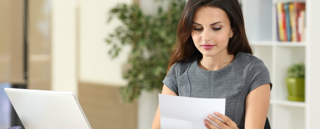 Young woman sitting in front of a computer and looking at a paper with credit card advance fees