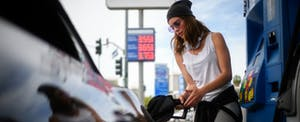 Young woman pumping gas after finding out how gas credit cards work