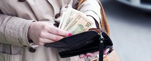 Woman counting cash from her wallet and contemplating claiming her unclaimed money