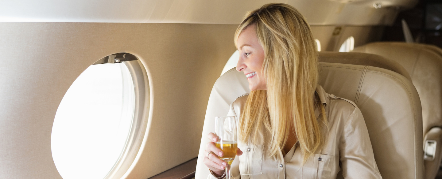 Young woman sitting in first class on an airplane and smiling because she knows that the 5 most exclusive credit cards are