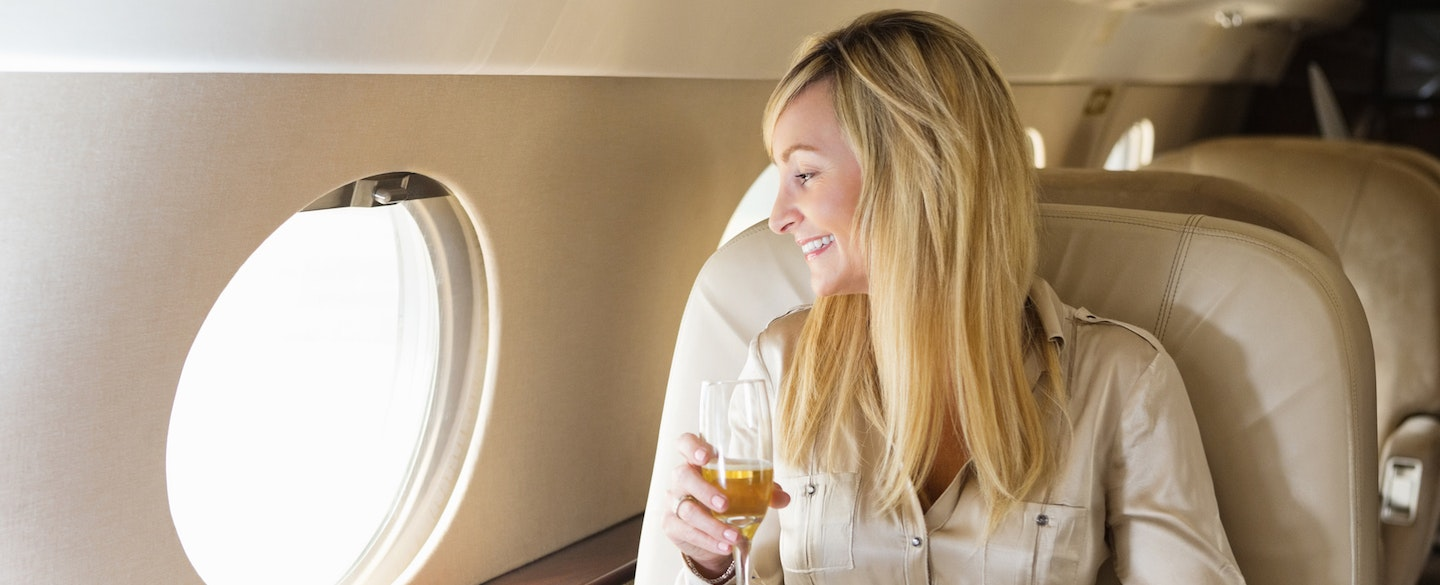 The 5 most exclusive credit cards credit karma young woman sitting in first class on an airplane and smiling because she knows that the stopboris Choice Image