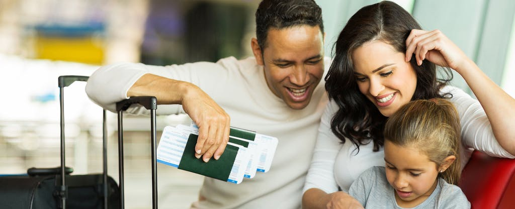 Young family gathered around a sheet learning about what they need to know about using debit cards internationally, waiting at an airport holding luggage, tickets, and passports.