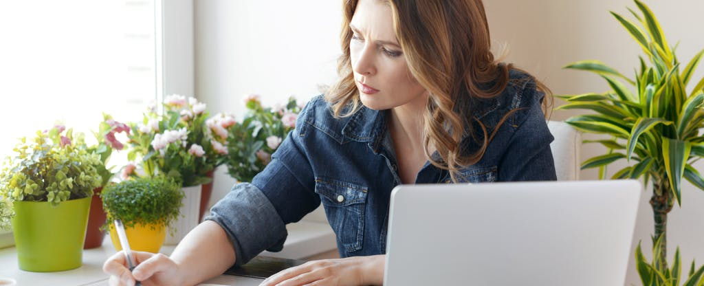 Woman sitting next to a computer and reading about if you should you pay the IRS with a credit card?