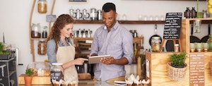 A man and a woman behind a coffee shop counter looking at a tablet to learn about the best credit cards for business owners and entrepreneurs