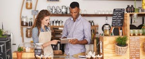 A man and a woman behind a coffee shop counter looking at a tablet to learn about the best business credit cards for business owners and entrepreneurs
