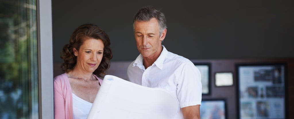 A mature couple looking at architectural plans together at home, wondering what mortgage points are.