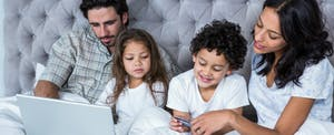 Young family sitting in bed, gathered around a laptop to learn what you need to know about credit card companies