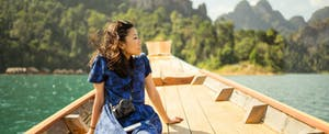 Young woman on a wooden boat in southeast Asia, contemplating what is the best Capital One credit card