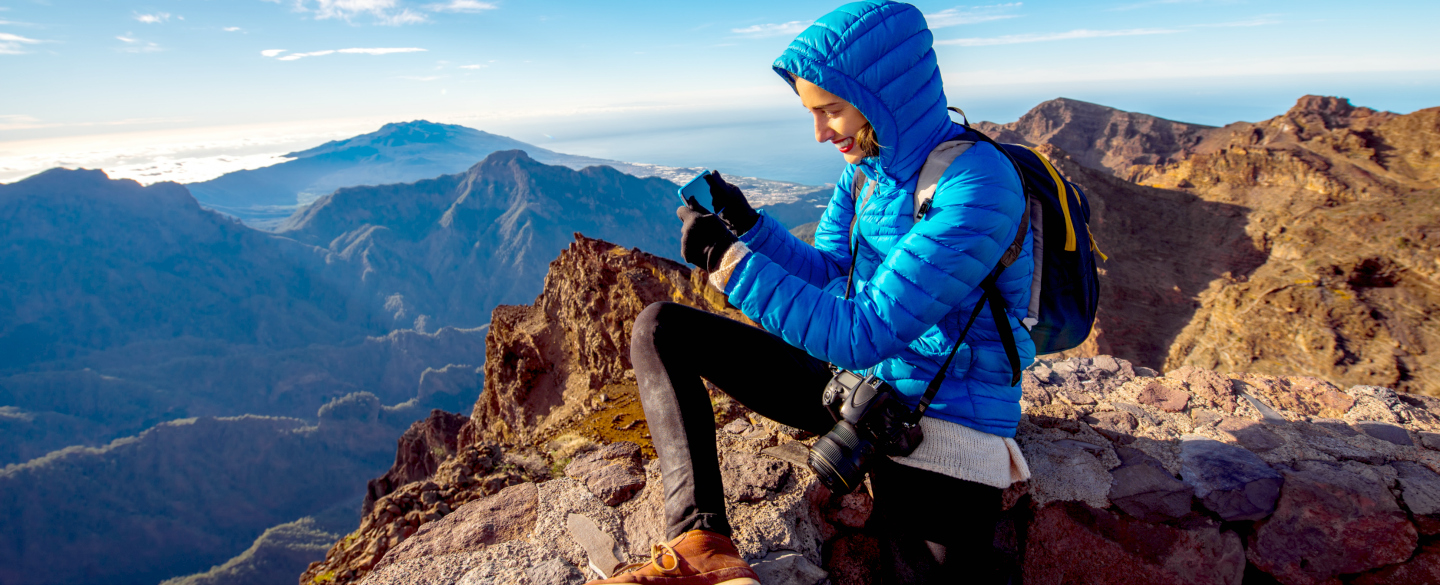 A woman on a mountain having a great time and totally unconcerned about how she'll pay for her trip because she already has the best barclaycard credit card for her