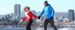 Young couple in winter gear running through a park with a cityscape in the background as they discuss the best PNC Bank credit cards