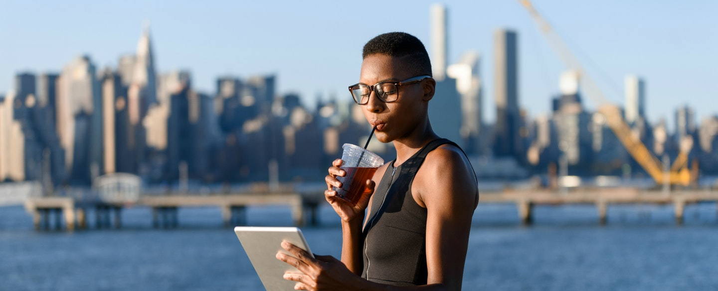 Woman On A Boardwalk Sipping Cold Drink And Using The Best Ways To