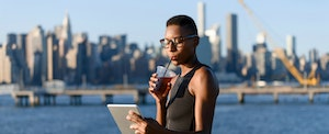 Woman on a boardwalk, sipping a cold drink, and using the best ways to send money transfers online on her tablet