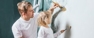 Father and young daughter painting a wall, while the father teaches her about credit card utilization and how it affects your credit score