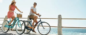 Young couple bicycling on a boardwalk and talking about how to get a credit card