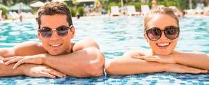 Young couple hanging off the edge of a pool and smiling because they compared platinum american express, chase sapphire reserve, and the citi prestige and ended up with the best card for them.