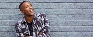 Man leaning against a brick wall and smiling because he just learned surprising facts about credit union credit cards