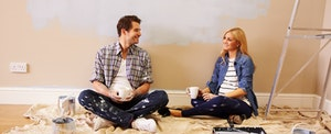 Young couple sitting on the floor, taking a break from painting, while discussing the best first national bank credit cards.