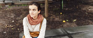 """Young woman sitting on a bench outside and wondering, """"Can a prequalification hurt my credit score?"""""""