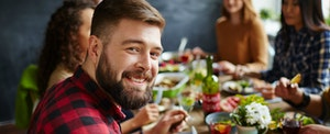 Young man at a festive dinner with friends, smiling because he finally settled the Chase Freedom vs. Chase Freedom Unlimited vs. Discover it debate