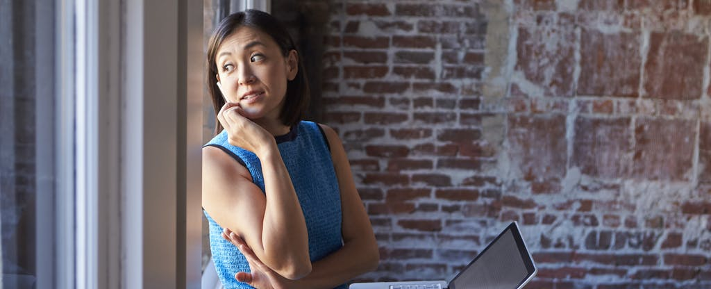 Woman looking out a window while leaning against a brick wall while wondering when credit card companies report to credit report bureaus