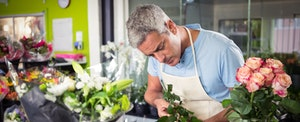 Man in his flower shop wondering if he should use a small business credit card