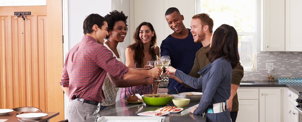 Group of young people toasting at a dinner party to celebrate a credit limit increase