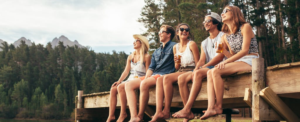 A group of friends sitting on a dock and discussing the 4 financial keys to adulting