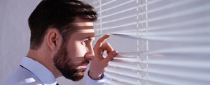 Man looking out a window with suspicion, wondering how hackers are going to use his stolen information