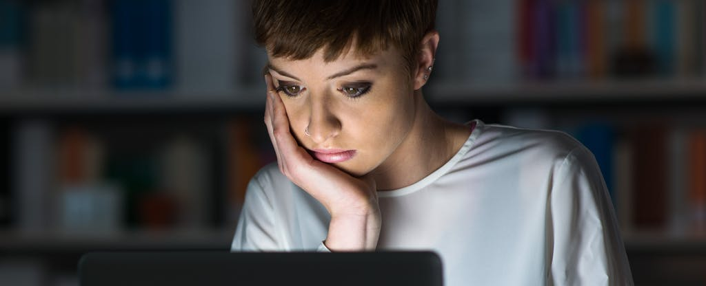 Young woman sitting in front of a glowing laptop and learning about how late payments can affect credit scores