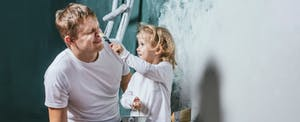 Dad painting a room with his daughter and explaining to her how to get a great mortgage rate