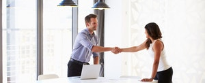 Man shaking hands with a job candidate who is wondering if an employer can check credit scores.